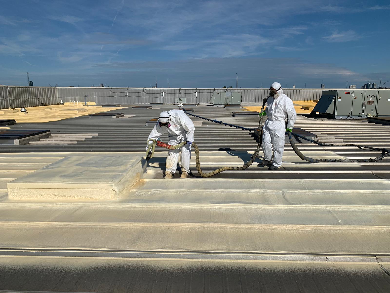 technicians installing roofing spray foam